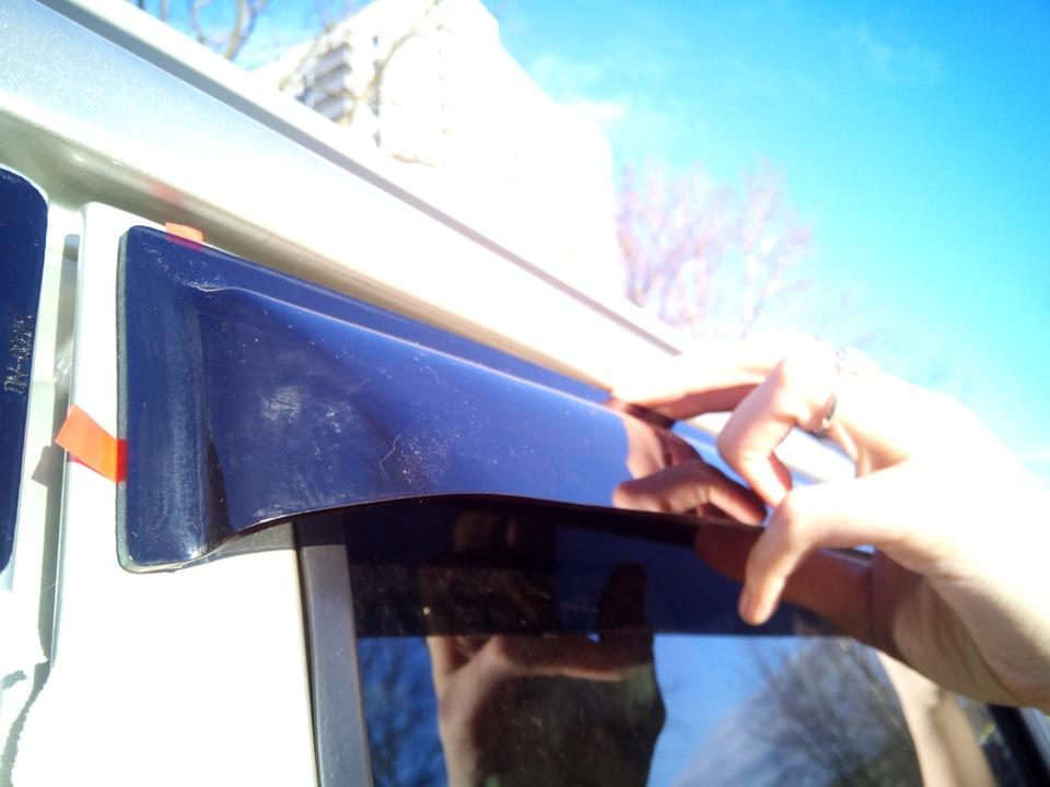 Процесс приклеивания ветровика к рамке окна